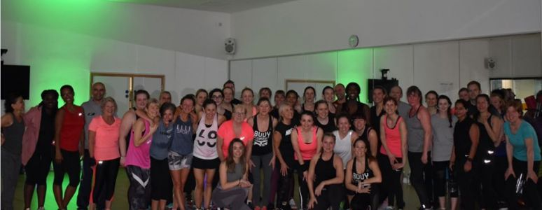 Group of people in fitness clothes, in a room lit with green spotlights